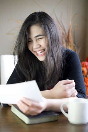 Teenage girl or young woman happily reading note in hand photo