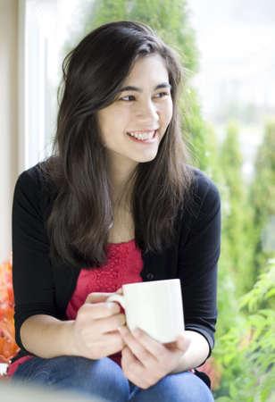 Beautiful biracial teenager or young woman drinking coffee next to window photo