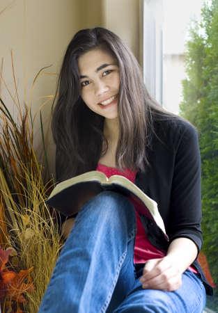 Mooie biracial tiener meisje studeren of lezen naast zonnige venster