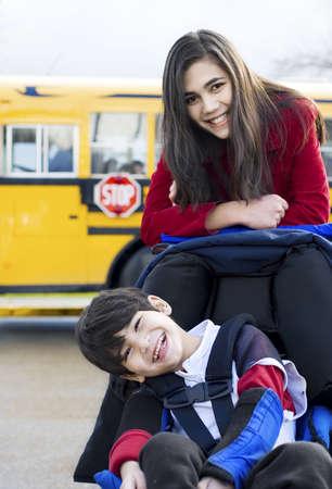 ni�o empujando: La hermana mayor con su hermano discapacitado en silla de ruedas en el autob�s escolar Foto de archivo