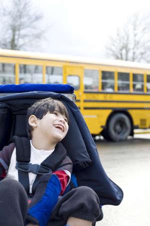 discapacidad: Discapacitados ni�o de cinco a�os de edad en silla de ruedas, por el autob�s escolar Foto de archivo