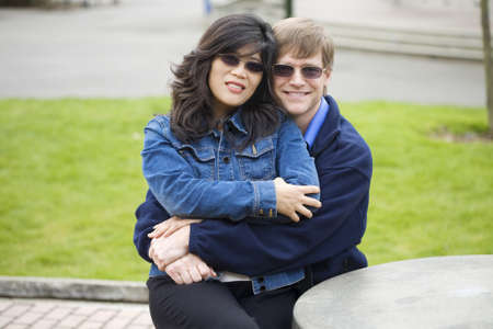 interracial marriage: Beautiful Caucasian, Asian couple sitting outdoors together, hugging.