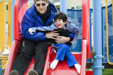 Vader naar beneden slide met gehandicapte zoon die heeft hersenverlamming Stockfoto