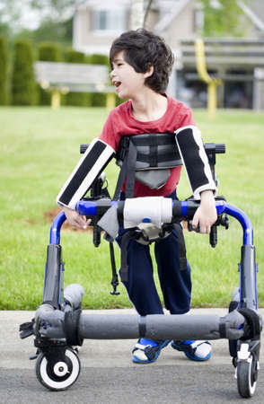 cerebral palsy: Five year old disabled boy in walker by park. He has cerebral palsy. Stock Photo