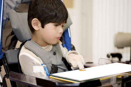 people with disabilities: Five year old disabled boy studying in wheelchair