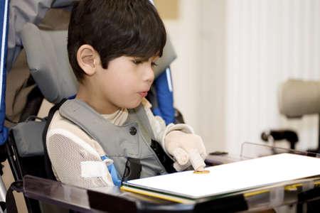 Vijf-jarige gehandicapte jongen studeren in rolstoel