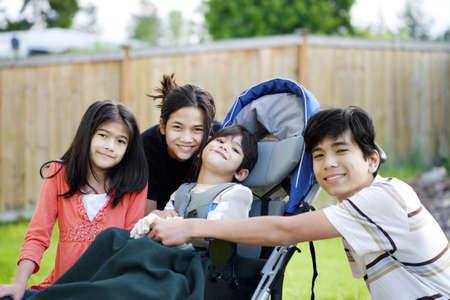 Vijf-jarige gehandicapte jongen in een rolstoel liefdevol omringd door zijn drie oudere broer en zussen