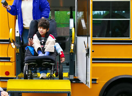 personas discapacitadas: Desactivado Niño cinco años utilizando un elevador de autobús para su silla de ruedas