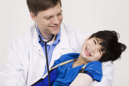 Male doctor in early forties holding five year old disabled patient during office visit photo