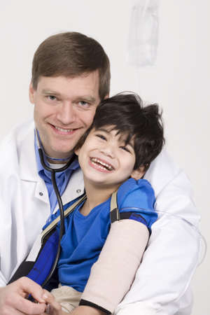 early forties: Male doctor in early forties holding five year old disabled patient during office visit
