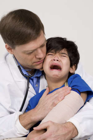 early forties: Male doctor in early forties comforting scared five year old disabled patient during office visit