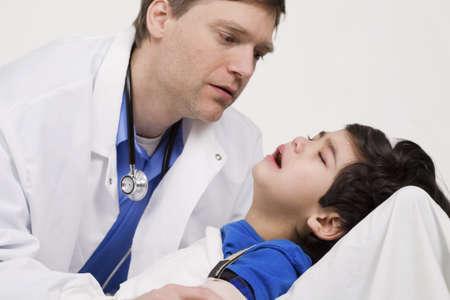 Mannelijke arts in de vroege jaren veertig troosten vijf jaar oude gehandicapte patiënt tijdens kantoor te bezoeken Stockfoto
