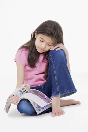 Ten year old Asian girl sitting on floor reading a magazine, isolated on white. All photos of flowers on magazine are those of the photographer herself. Use allowed. photo