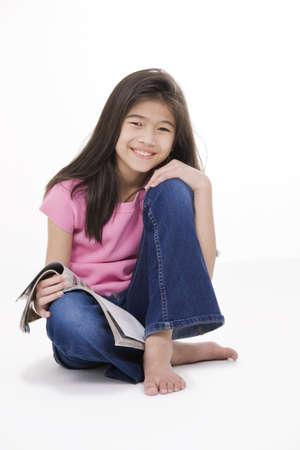 Tien jaar oude Aziatische meisje zitten op de vloer een tijdschrift te lezen, geïsoleerd op wit