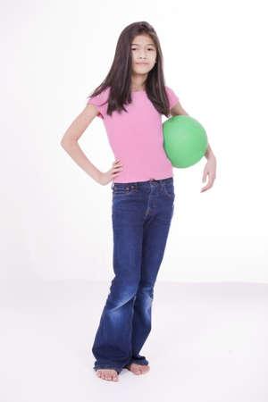 Tien jaar oude Aziatische meisje met groene bal met uitdagende houding, geïsoleerd op wit Stockfoto