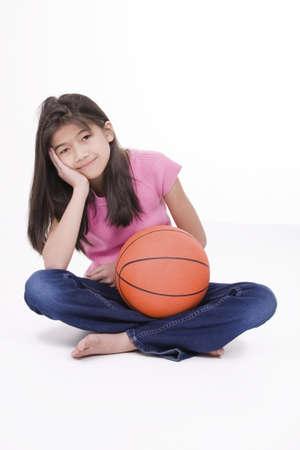 baloncesto chica: Ni�a de diez a�os de baloncesto asi�tico sentado en piso de la celebraci�n, aislado en blanco