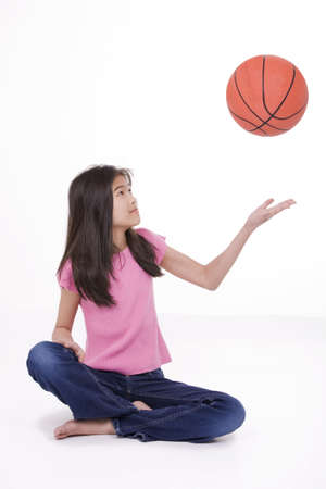 Ten year old Asian girl sitting on floor throwing basketball up in the air, isolated on white photo