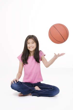 Tien jaar oude Aziatische meisje zitten op de vloer gooien basketbal omhoog in de lucht, geïsoleerd op wit Stockfoto