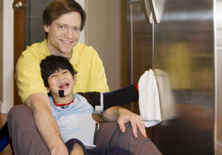 cerebral palsy: Father on kitchen floor with disabled son, cleaning the fridge. Son has cerebral palsy, with leg orthotics and arm splints. Stock Photo
