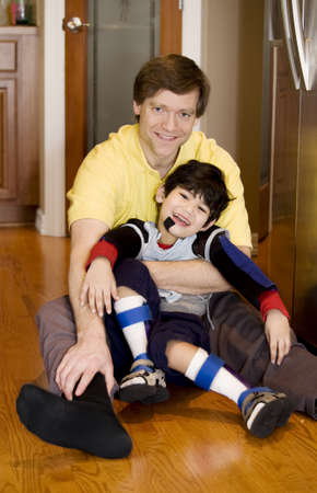 Father holding disabled son on kitchen floor. Son has cerebral palsy. Stock Photo