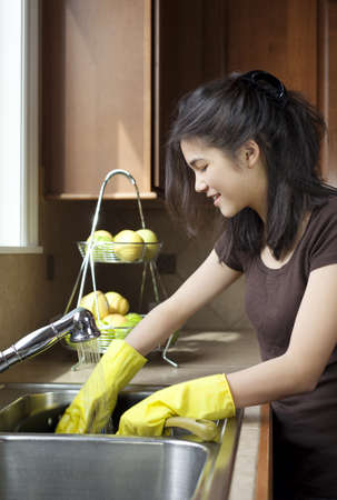 dishwashing: Teen girl washing dishes at kitchen sink