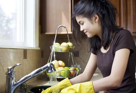 La muchacha adolescente lavar los platos en el fregadero de la cocina