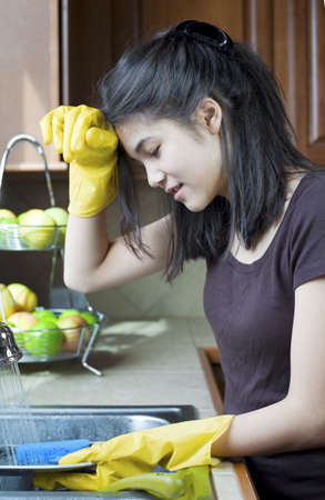 Teen girl washing dishes at kitchen sink, tired expression. photo