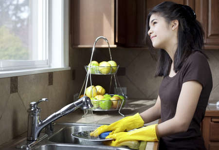 Teen girl washing dishes at kitchen sink, daydreaming or looking out the window with thoughtful expression.