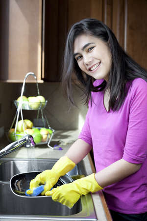 Teen girl happily washing dishes at kitchen sink photo