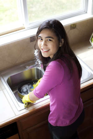 Teen girl happily washing dishes at kitchen sink Stock Photo