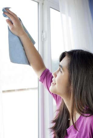 Biracial Aziatische, Kaukasische tiener of jonge vrouw schoonmaken interieur thuis ramen