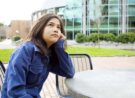 Twelve year old girl sitting at outdoors table looking up into sky with thoughtful expression, head on hand