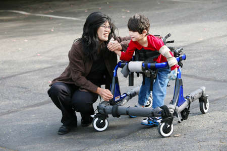 Mother with disabled son walking outdoors with walker, medical mobility equipment Stockfoto