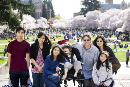 Multiracial family of seven in front of crowded field of cherry blossom trees. Youngest child is disabled with cerebral palsy. photo