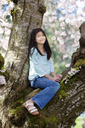 Ten year old biracial girl sitting in cherry tree covered in blossoms Stock Photo - 13562814