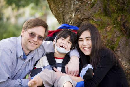 Gelukkig gehandicapte jongen met een hersenverlamming in een rolstoel, omringd door vader en oudere zus, lachen