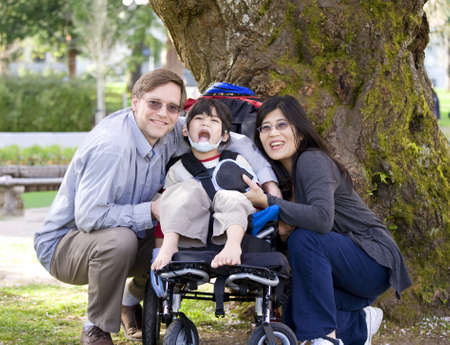 cerebral palsy: Happy disabled child in wheelchair surrounded by parents, outdoors. Cerebral palsy.