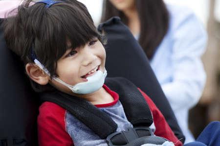 Gelukkig vijf jaar oude gehandicapte jongen in een rolstoel en beschermende kleding Stockfoto