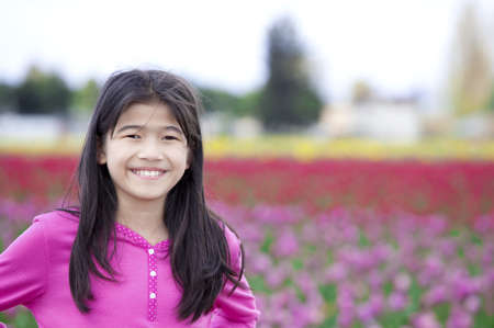 asian tulips: Biracial ten year old girl happily standing in front of tulip field Stock Photo