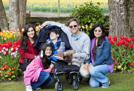Interracial family in tulip gardens sitting near disabled boy in wheelchair