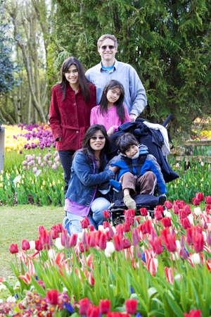 Interraciaal familie in tulp tuin zitten in de buurt gehandicapte jongen in een rolstoel. Stockfoto