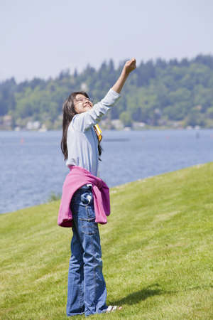Biracial asian girl flying kite by the lake photo