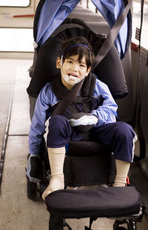 Disabled little preschool boy in wheelchair on bus. Child has cerebral palsy. photo