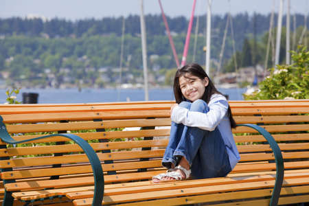 hugging knees: Happy ten year old girl enjoying the sun on bench by the lake Stock Photo