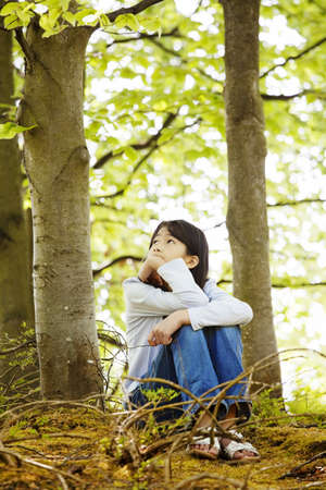 Ten year old girl sitting quietly in woods, looking around thinking photo