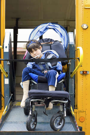 Disabled little boy on school bus wheelchair lift photo