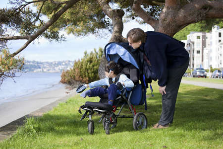 Father spending time with disabled son in wheelchair at the lake Stock Photo - 14505770