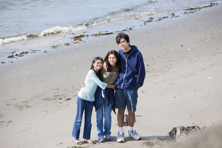 Brother and sisters standing on beach hugging photo