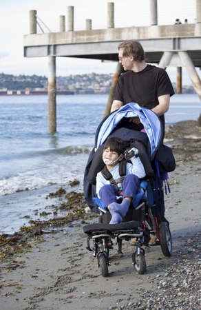 Father pushing wheelchair with disabled son on beach photo