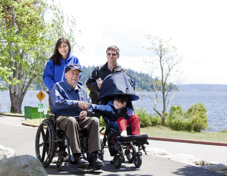 Family with disabled senior and child walking outdoors photo